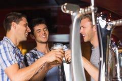Lyckliga vänner som rostar med halva liter av öl Fotografering för Bildbyråer