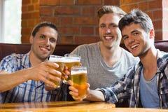 Lyckliga vänner som rostar med halva liter av öl Royaltyfri Foto