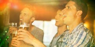 Lyckliga vänner som rostar med halva liter av öl på patricksdag Royaltyfria Bilder