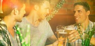 Lyckliga vänner som rostar med halva liter av öl på patricksdag Arkivfoton