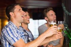 Lyckliga vänner som rostar med halva liter av öl på patricksdag Royaltyfri Bild