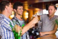 Lyckliga vänner som rostar med halva liter av öl på patricksdag Arkivfoto