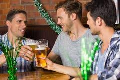 Lyckliga vänner som rostar med halva liter av öl på patricksdag Fotografering för Bildbyråer