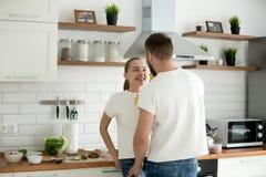 Lyckliga vänner som ser i ögon som tycker om intimitetmatlagning, frukosterar royaltyfria bilder
