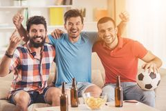 Lyckliga vänner som sitter på Sofa Watching Football Fotografering för Bildbyråer