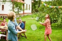Lyckliga vänner som spelar badminton på sommarträdgården Fotografering för Bildbyråer