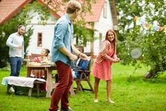 Lyckliga vänner som spelar badminton på sommarträdgården Arkivfoto