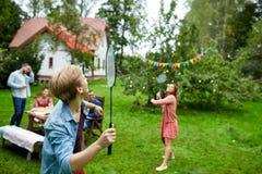 Lyckliga vänner som spelar badminton på sommarträdgården Royaltyfri Bild