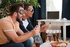 Lyckliga vänner som spelar dataspelar Arkivfoto