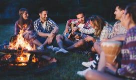 Lyckliga vänner som spelar musik och tycker om brasan Royaltyfria Bilder