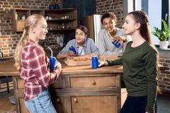 Lyckliga vänner som spenderar tid samman med pizza- och sodavattendrinkar Fotografering för Bildbyråer
