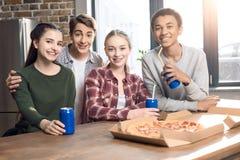 Lyckliga vänner som spenderar tid samman med pizza- och sodavattendrinkar Arkivbild