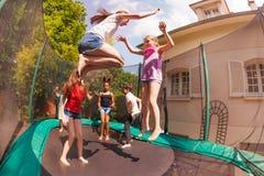 Lyckliga vänner som studsar på den utomhus- trampolinen royaltyfri foto