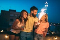 Lyckliga vänner som tänder tomtebloss och tycker om frihet Royaltyfria Foton