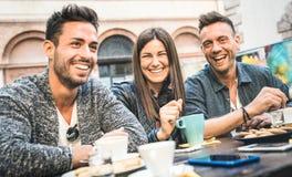 Lyckliga vänner som talar och har gyckel på att dricka för barrestaurang arkivfoton
