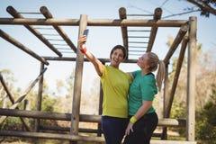 Lyckliga vänner som tar selfie i kängaläger Royaltyfri Bild
