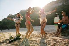 Lyckliga vänner som tycker om på stranden och dansa Arkivfoto