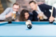 Lyckliga vänner som tycker om spela snookerleken och dricka öl arkivbild
