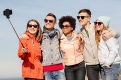 Lyckliga vänner som utomhus tar selfie vid smartphonen royaltyfri fotografi