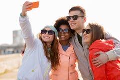 Lyckliga vänner som utomhus tar selfie vid smartphonen fotografering för bildbyråer
