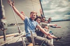 Lyckliga vänner som vilar på en yacht Royaltyfri Bild