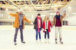 Lyckliga vänner som vinkar händer på att åka skridskor isbanan Royaltyfri Fotografi