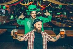 Lyckliga vänner står i bar och poserar på kamera De ser raka Grabben i grön dräkt visar upp hans stora tummar Grön treesbakgrund royaltyfria foton