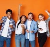 Lyckliga vänner Studenter med telefoner som skriker över bakgrund royaltyfria bilder