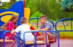 Lyckliga vänner, ungar som har gyckel på karusell på lekplatsen royaltyfria bilder