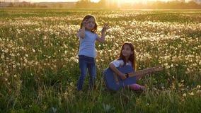 Lyckliga vårdagar Två roliga attraktiva lilla systrar som sjunger och spelar den akustiska jeansgitarren i äng flickor som har gy stock video