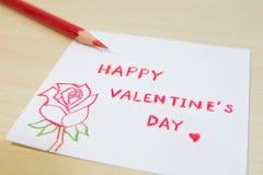 Lyckliga valentin dagformuleringar i litet papper med den röda färgpennan Arkivbilder