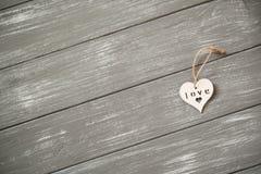 lyckliga valentiner för bakgrundsdag Dekorativ vit trähjärta på grått lantligt Begrepp för valentin` s Arkivbild
