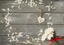 lyckliga valentiner för bakgrundsdag Dekorativ vit trähjärta på grått lantligt, whith blommar, begreppet för valentin` s Royaltyfri Foto