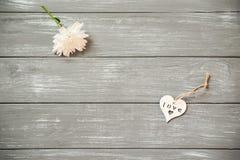 lyckliga valentiner för bakgrundsdag Dekorativ vit trähjärta på grått lantligt, whith blommar, begreppet för valentin` s Arkivbild