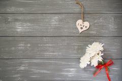 lyckliga valentiner för bakgrundsdag Dekorativ vit trähjärta på grått lantligt, whith blommar, begreppet för valentin` s Arkivbilder