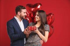 lyckliga valentiner för dag Pojken ger en gåva till hans flicka Fotografering för Bildbyråer