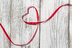 lyckliga valentiner för dag Röd bandhjärta på vit träbakgrund Arkivfoton
