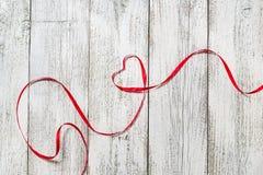 lyckliga valentiner för dag Röd bandhjärta på vit träbakgrund Royaltyfri Foto