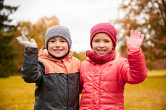 Lyckliga vinkande händer för flicka och för pojke i höst parkerar Royaltyfri Foto