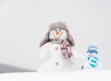 Lyckliga vintersnögubbear familj eller vänner Arkivfoto