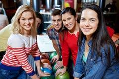 Lyckliga vänner i bowlingklubba Royaltyfria Bilder
