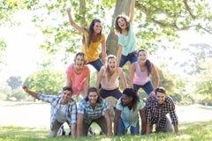 Lyckliga vänner i parkera som gör den mänskliga pyramiden Royaltyfri Foto