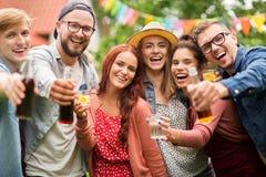Lyckliga vänner med drinkar på det trädgårds- partiet för sommar Arkivbilder