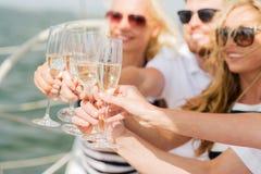Lyckliga vänner med exponeringsglas av champagne på yachten Arkivbild