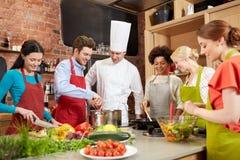 Lyckliga vänner och kocken lagar mat matlagning i kök Arkivbild