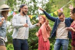 Lyckliga vänner som dansar på sommar, festar i trädgård Arkivbild