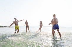 Lyckliga vänner som har gyckel på sommarstranden Fotografering för Bildbyråer