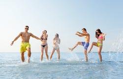 Lyckliga vänner som har gyckel på sommarstranden Arkivfoton