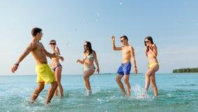 Lyckliga vänner som har gyckel på sommarstranden Royaltyfri Foto