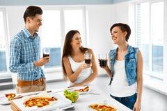 Lyckliga vänner som har hemmet för matställeparti Äta mat, kamratskap Royaltyfri Fotografi